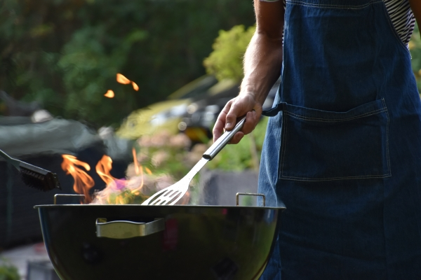 Man grilling food over an flaming grill in his backyard.